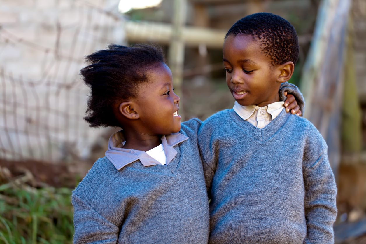 Two children arm in arm